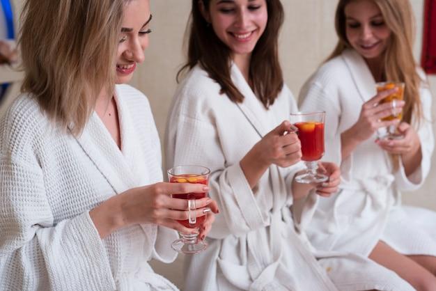 Mujeres que prueban bebidas saludables en el spa