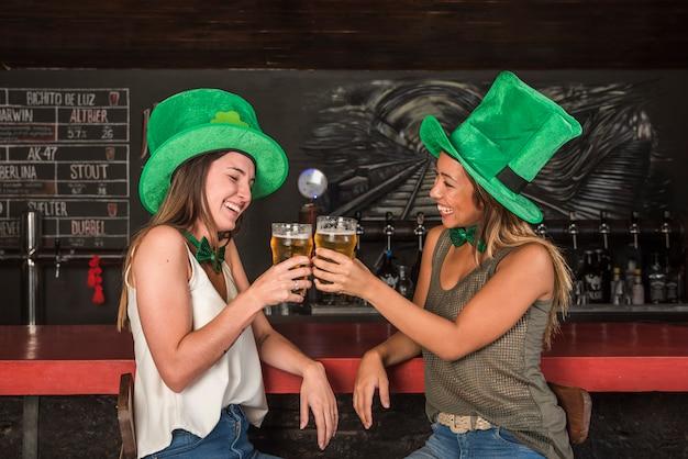 Mujeres que ríen en los sombreros de san patricio con copas de bebida en la barra del bar