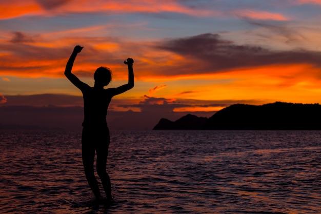 Mujeres que son felices en el mar con cielo dorado.