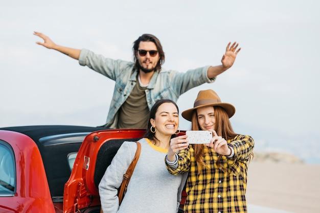 Mujeres que toman autofotos en un teléfono inteligente cerca del maletero del coche y el hombre que se inclina hacia fuera del auto