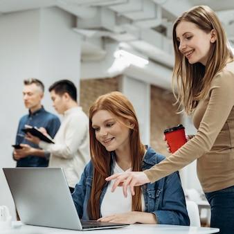 Mujeres que trabajan juntas en un proyecto en la oficina.
