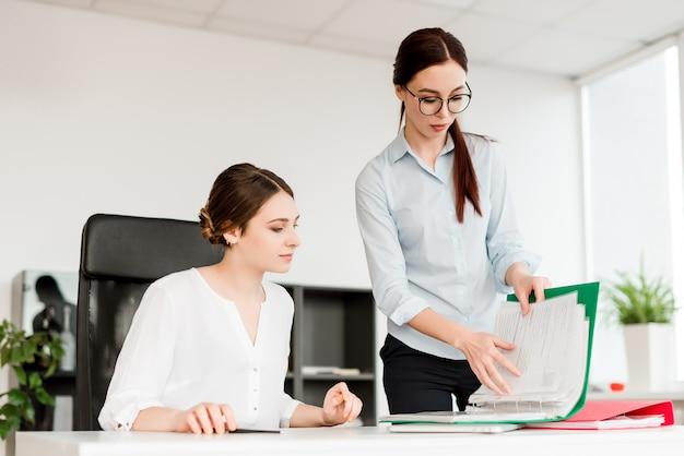 Mujeres que trabajan en la oficina y firman documentos comerciales