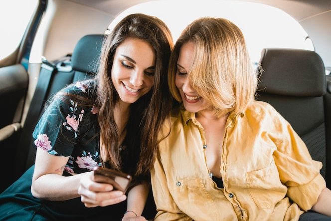 Mujeres que usan el teléfono inteligente en el coche