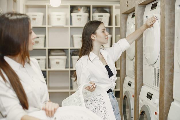 Mujeres que usan lavadora lavando la ropa. chicas jóvenes dispuestas a lavar la ropa. interior, concepto de proceso de lavado