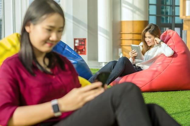 Mujeres que usan redes sociales cada equipo de tecnología en la oficina creativa moderna