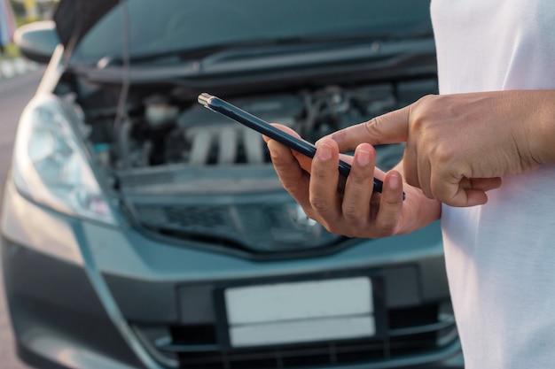 Mujeres que usan el teléfono móvil para tomar fotos de su auto que abre el capó.