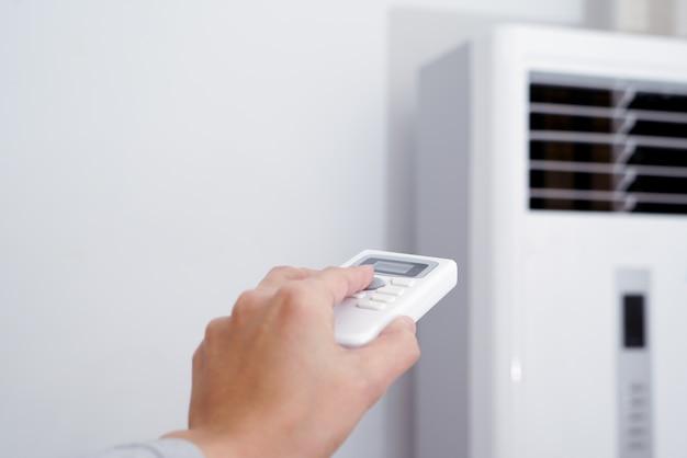 Las mujeres regulan a mano el calentador / aire acondicionado