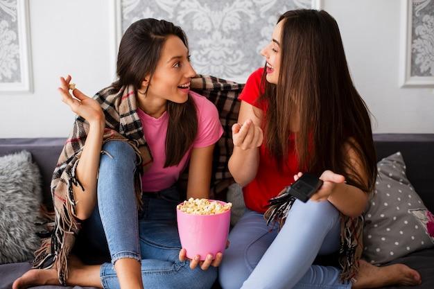 Mujeres relajándose en casa y comiendo palomitas de maíz