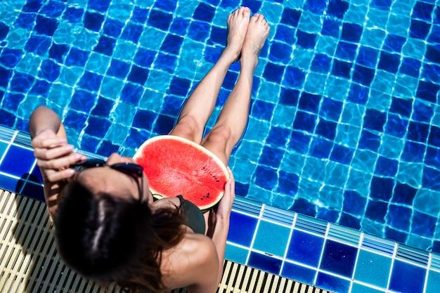 Mujeres relajantes y sosteniendo watermalon en la piscina.