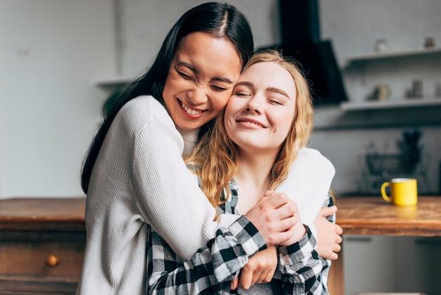 Mujeres riendo abrazando en casa