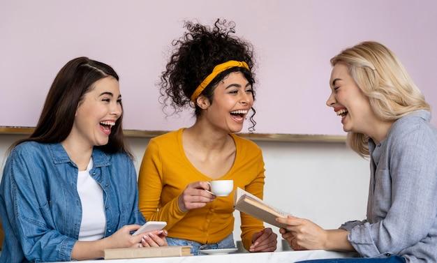 Mujeres riendo felices tomando café
