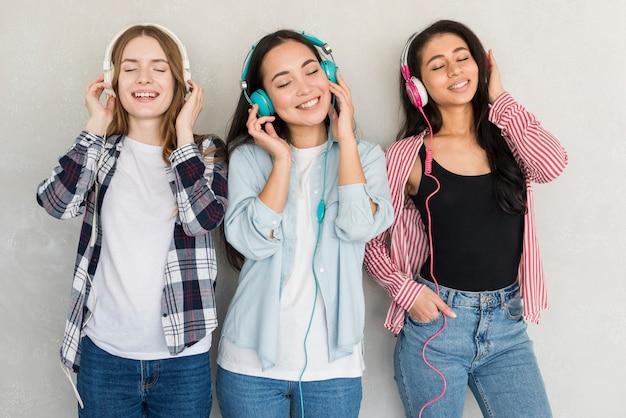 Mujeres riendo de pie y escuchando música en auriculares de colores