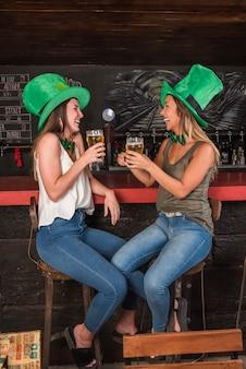 Mujeres riendo en los sombreros de san patricio con vasos de bebida en la barra del bar