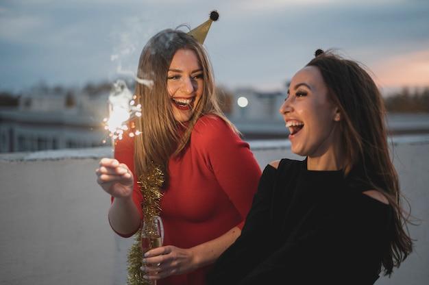 Mujeres riendo sosteniendo las bengalas