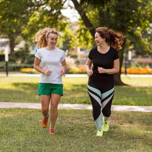 Mujeres en ropa deportiva corriendo juntos afuera