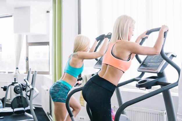 Las mujeres en ropa deportiva con máquina de paso