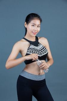 Mujeres en ropa deportiva sostienen una botella de agua potable.