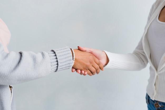 Mujeres en ropas pálidas dándose la mano en saludo.