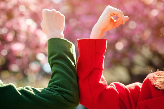 Mujeres saludando con los codos al aire libre. concepto de distanciamiento social. dos chicas topando los codos en el parque de la primavera.