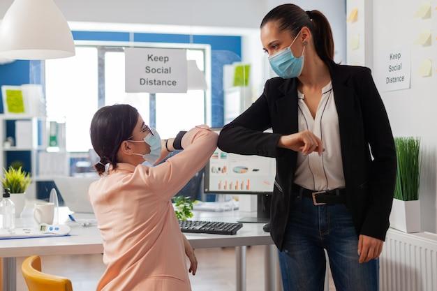 Mujeres saludando en la nueva oficina normal tocándose los codos chocando manteniendo el distanciamiento social como prevención de seguridad usando mascarilla durante la pandemia global con covid19.