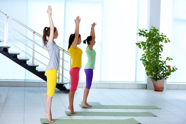 Las mujeres sanas hacen ejercicios de yoga en un gimnasio.