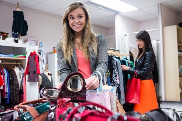 Mujeres seleccionando bolsos y ropa mientras compran