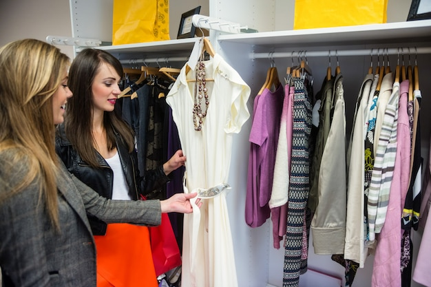 Mujeres seleccionando un vestido mientras compran ropa