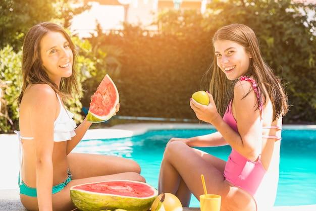 Mujeres sentadas en borde de piscina con frutas