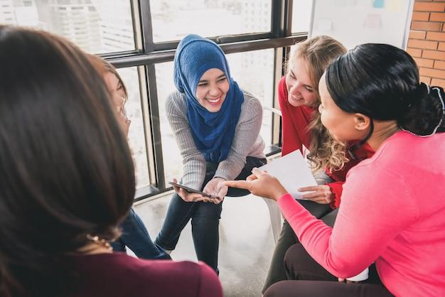 Mujeres sentadas en círculo disfrutando compartiendo historias en una reunión grupal