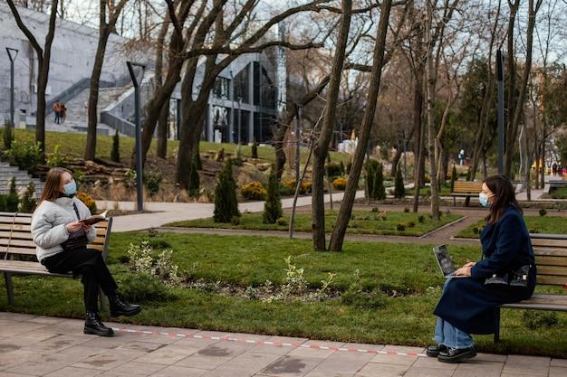 Mujeres sentadas a distancia y con máscara