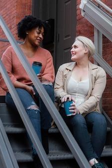 Mujeres sentadas en las escaleras full shot