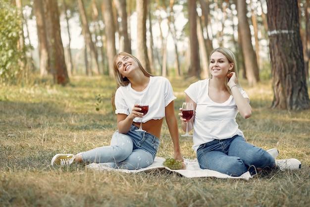 Mujeres sentadas en un picnic y bebiendo vino