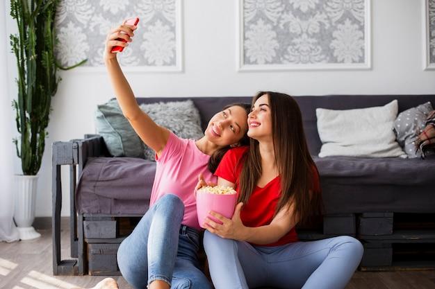 Mujeres sentadas en el piso y tomando selfie