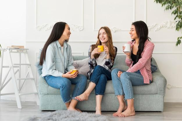 Mujeres sentadas en el sofá y charlando sosteniendo tazas en la mano