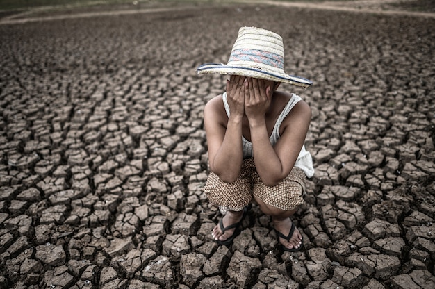 Las mujeres sentadas en sus manos, cerraron sus rostros en tierra seca en un mundo en calentamiento.