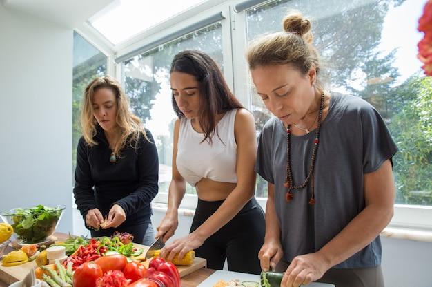 Mujeres serias cocinando y cortando verduras en la cocina.