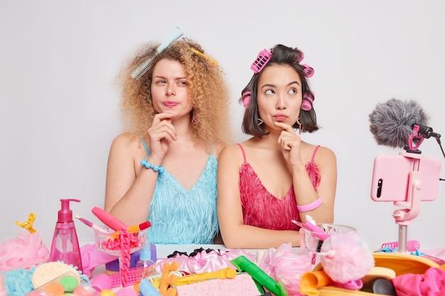 Mujeres serias y reflexivas enfocadas en algún lugar con expresiones pensativas hacen que el peinado grabe video en vivo hablar sobre productos cosméticos cómo cuidar de ti mismo hacer series en línea para la audiencia