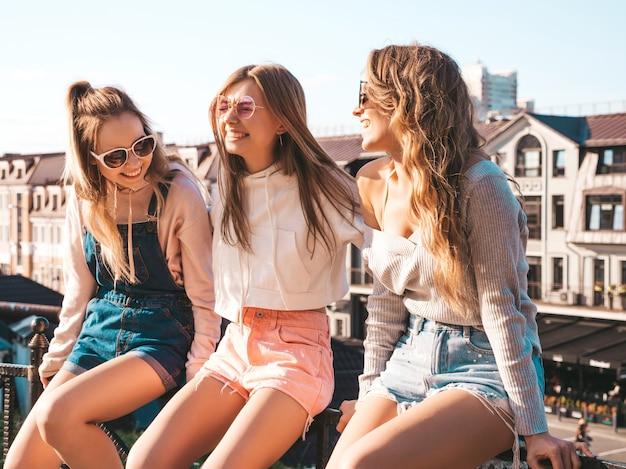 Mujeres sexy sentadas en pasamanos en la calle se comunican y discuten algo