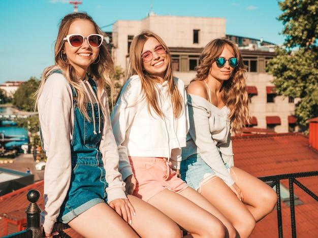 Mujeres sexy sentadas en pasamanos en la calle. modelos positivos divirtiéndose en gafas de sol. comunicando y discutiendo algo