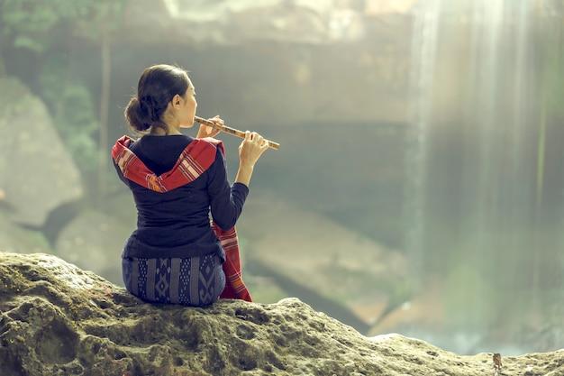 Las mujeres se sientan cómodamente la flauta en el bosque con una cascada, nhongkhai, tailandia.