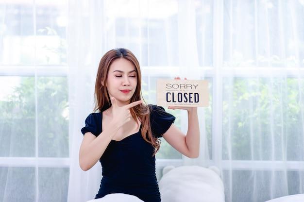 Mujeres y signos de cierre de tiendas concepto de cierre y cancelación de negocios