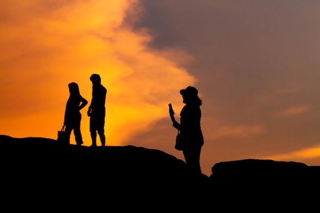Mujeres silueta fotografía y selfie con la montaña al atardecer.