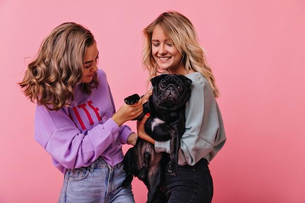 Mujeres soñadoras jugando con lindo cachorro de bulldog en pastel. chicas románticas disfrutando de un buen día y posando con mascota.