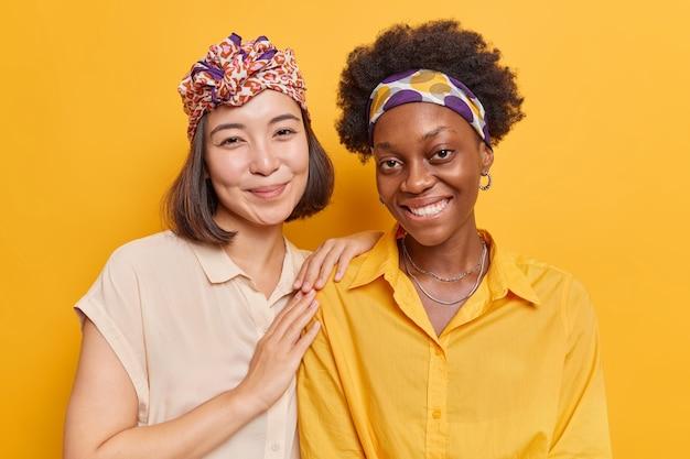 Las mujeres sonríen gratamente pasar el tiempo libre juntas se extrañaron vestidas casualmente aisladas en amarillo