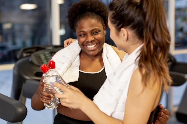 Mujeres sonrientes de alto ángulo en el gimnasio