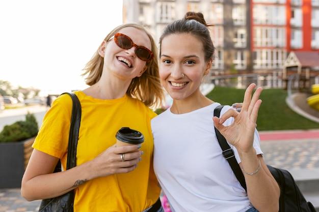 Mujeres sonrientes en la ciudad usando lenguaje de señas