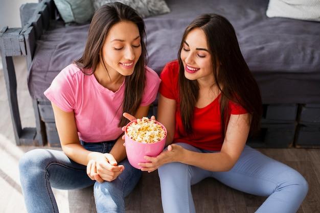 Mujeres sonrientes compartiendo palomitas de maíz