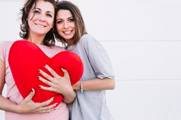 Mujeres sonrientes con corazón afelpado mirando a la cámara