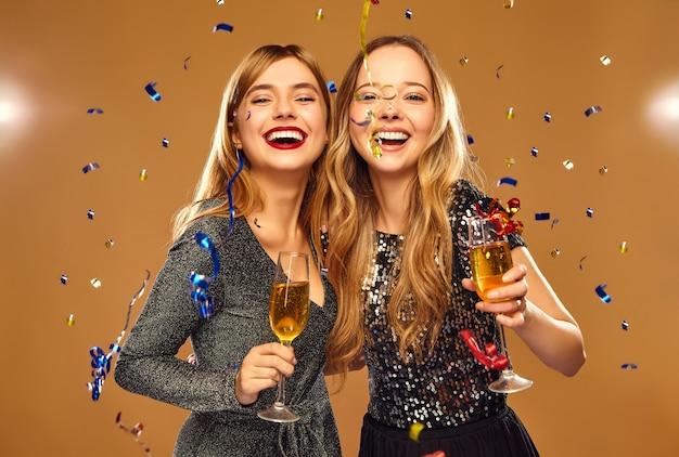 Mujeres sonrientes felices en elegantes vestidos glamorosos con copas de champán bajo confeti