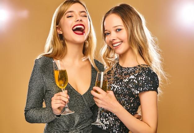 Mujeres sonrientes felices en elegantes vestidos glamorosos con copas de champán en la pared de oro